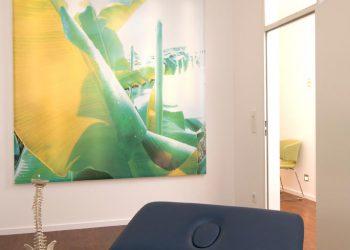 Behandlungsraum mit Liege und Bild im Hintergrund